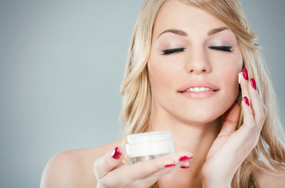 Woman Applying Lotion with Hyaluronic Acid